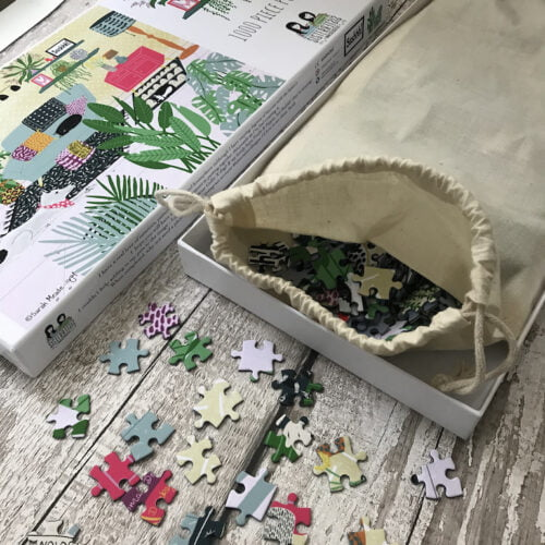 Photograph shows Sister Sister's 1000 piece jigsaw puzzle called Ssshhh! as an open box with some jigsaw pieces scattered on the table. A cotton pull string bag is sitting in the bottom half of the box with all the pieces in it and the lid with the design on is laid on the table to the side of the bottom half of the box
