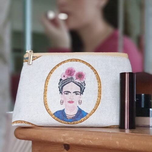 lifestyle photo of a polished metal zip bag in a natural fabric with a stylised portrait of Frida Kahlo printed on the fabric
