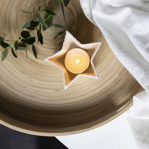Star porcelain tea light holder, lit on a wooden tray.