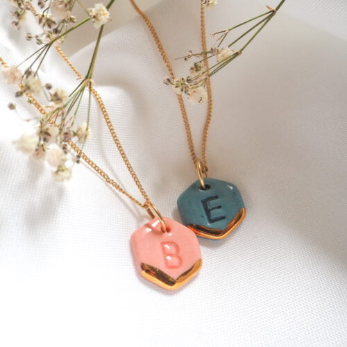 blue and pink hexagons with letters imprinted, gold lustre stripes and attached to gold chains