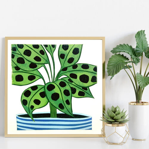 Maranta Plant Lino Print in a square light wooden frame on white shelf next to two plants