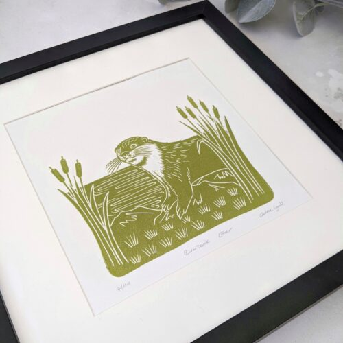 Linocut print of an otter on a riverbank framed by bullrushes in green - rose and hen