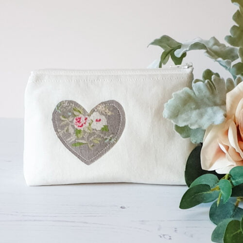 Medium sizw zip bag with boxy corners in cream with a vintage style rose heart applique on the front