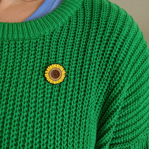 Yellow Sunflower Enamel Pin being worn on chunky green knit jumper