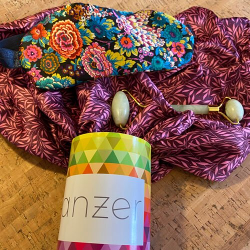 Silk pillowcase spilling out of Anzer can, with silk eye mask laid on top and jade facial roller