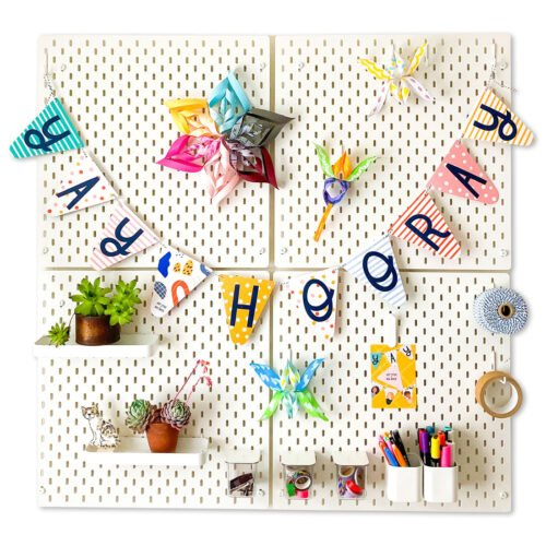 colourful paper bunting with the words Yay Hooray hanging on white pegboard with an assortment of colourful decorations, plants and stationery items