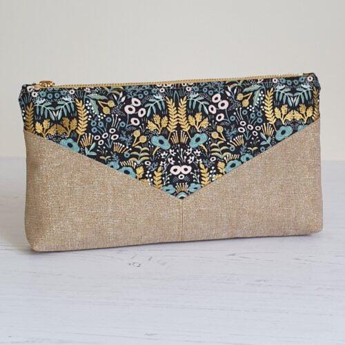 Oblong clutch purse in 2 coordinating metallic fabrics sewn in a V pattern