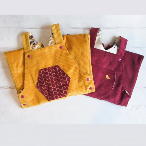 An image showing a pair of gold corduroy dungarees, with a hand embroidered honeycomb pocket, folded on top of a pair of dark red corduroy dungarres with a gold birth embroidered in the top right of the pocket.