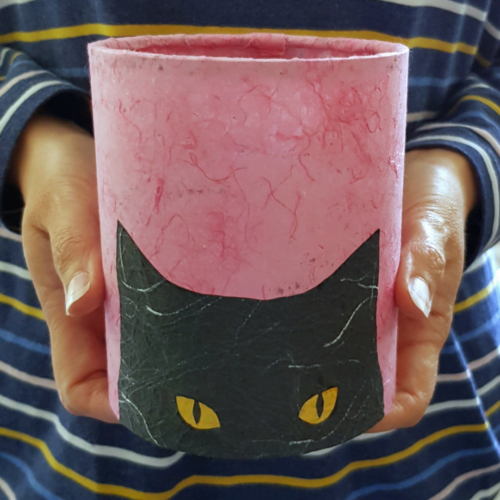 PeachTreePig - An LED lantern with a peeking black cat silhouette head on a pink background. Being held in hands (© PeachTreePig)