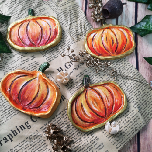 Four clay, hand painted pumpkin trinket trays on newscript with seed pods and dried flora scattered around them.