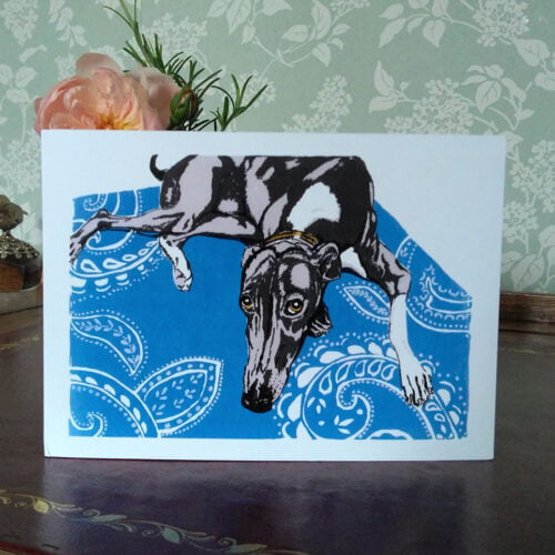 Anita Saunders Artist Favourite Rug greetings card. An original srtwork of a whippet dog on a bright blue patterned rug