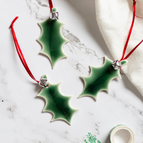 Rachel Carpenter Ceramics, Porcelain Green Holly Leaves with a red ribbon.