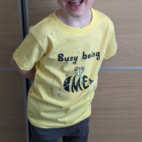 Smiling boy wearing a yellow t-shirt with a bee printed on it. The slogan reads Busy being ME.