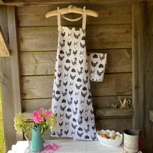 100% cotton apron and tea towel with black and white chicken pattern hanging on rustic wooden wall
