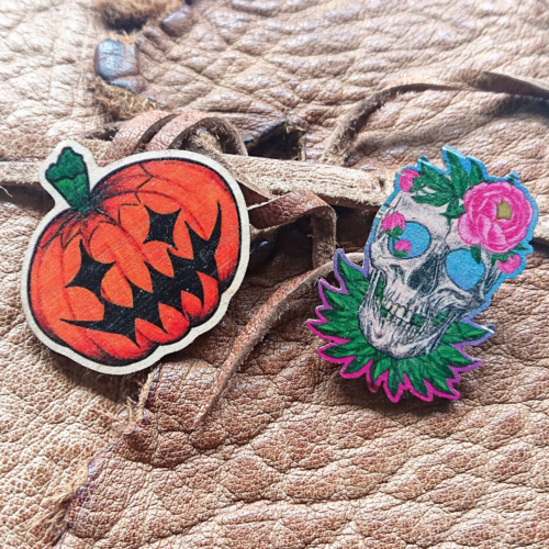 Hannah Kate Makes, two wooden pins. One orange pumpkin and one skull surrounded by peonies.