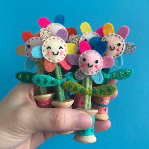 Handful of felt flowers in bright colours against a blue background