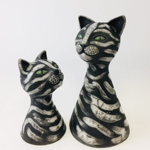 2 black and white ceramic cat sculptures