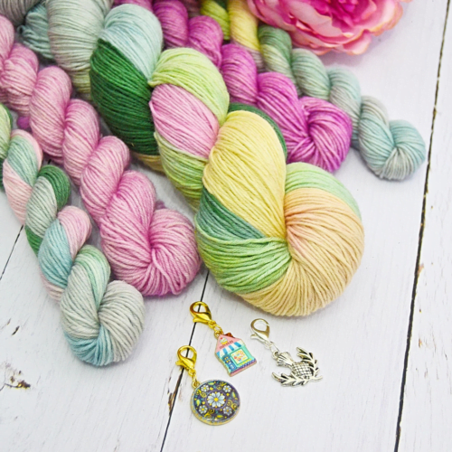 Multiple skeins of hand-dyed wool and three stitch markers on table