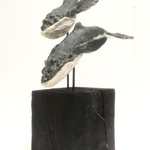 two humpback whales made in clay diving of a block of wood