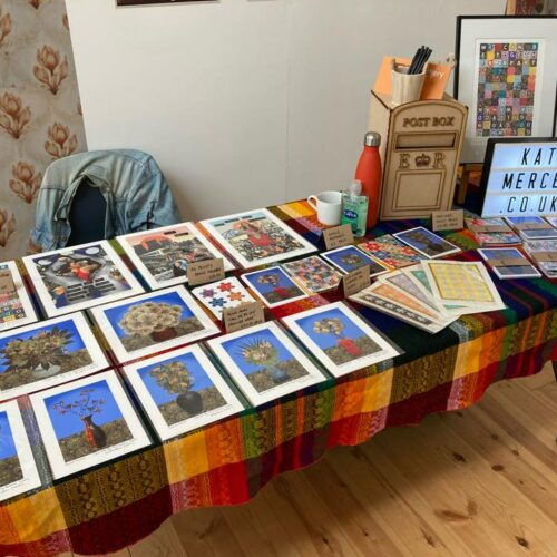 Kate Mercer Art & Photography - a trestle table layed out with prints and postcards of digital montages made by the artist