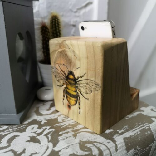 Wooden phone or tablet stand in natural wood with Bee decoration on the back face.
