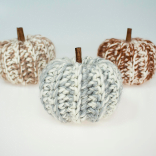 Three handmade crochet pumpkins. Each pumpkin is a different colour, the one on the left is brown, the one in the middle is grey and the one on the right is orange. Each pumpkin has a wooden stick in the top to represent it's stalk.