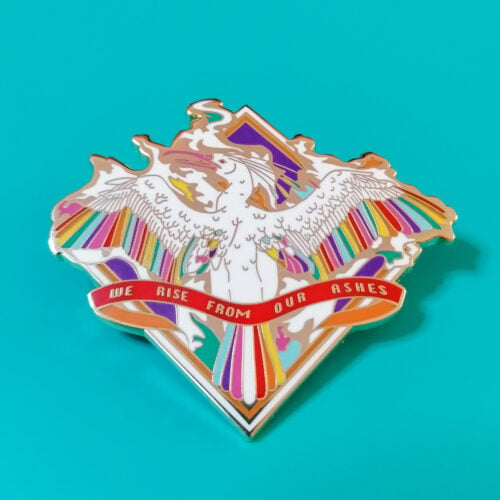 An enamel pin featuring a white phoenix with wings spread, inside a square-diamond shape. The phoenix has rainbow. hued feathers in wings and tail, is surrounded by flames in the same colours, and has a banner over its tail reading 'we rise from our ashes'.